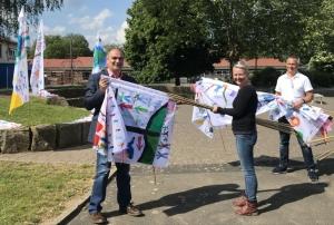 Schulsozialarbeitern Julia Jespers übergibt die Flaggen an den Bürgermeister Klaus Gier
